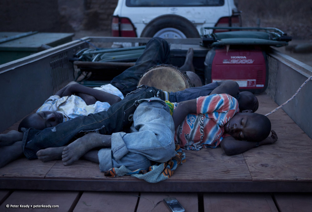 Young boys sleep in the bed of an equipment wagon in the early light of an African morning. Burkina Faso, Africa.