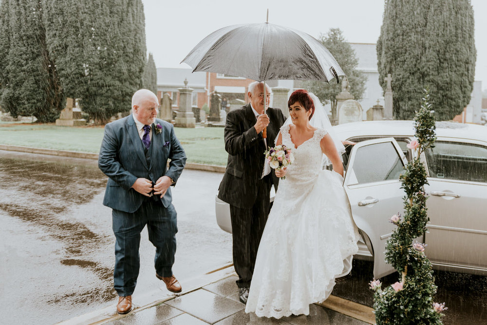 bride arrives at church in the rain