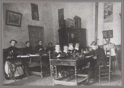 Recreatiekamer in het Burgerweeshuis, met 4meisjes, 4jongens en de weeshuisvader en -moeder. Circa 1889-1914