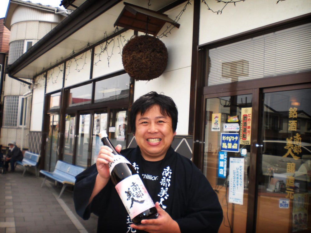 "Kuramoto, 5th Generation Owner of Nanbu Bijin    Kosuke Kuji  was born in 1972, the eldest son of Hiroshi Kuji, the 4th generation owner of Nanbu Bijin Brewery.  Kosuke Kuji studied the art of making sake and shochu at the prestigious Tokyo University of Agriculture, learning from professor Takeo Koizumi, who is a well regarded authority on fermented foods. Nanbu Bijin sake has received many awards in national and international sake competitions and also were the first to create a certified Kosher and ""no sugar added"" plum sake made with only koji rice and locally sourced green plums from Iwate. Kosuke Kuji is well regarded in the sake industry as a strong community supporter of the Tokhoku region of Japan and as an energetic, enthusiastic speaker about all things sake.  His enthusiasm and hard work have won over many people to try and then love sake.  飲んだ時に笑顔あふれる太陽のような酒 ""I want to brew sake that makes people smile like the sun shines."" - Kosuke Kuji"