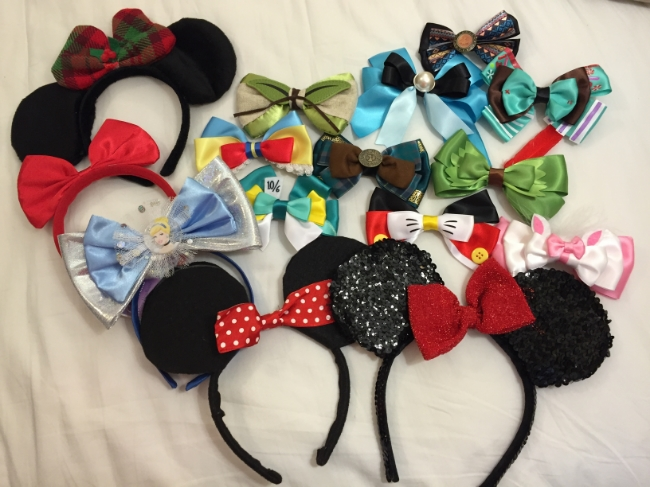 My collection of ears & bows (Christmas ears from Walmart, Cinderella ears from Party City, Minnie ears on the left are DIY, sequin Minnie ears on the right are from WDW, bows are from Hot Topic)