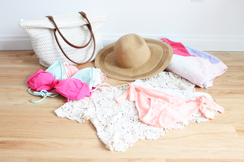 Beach essentials left to right: beach bag, bikinis, sun hat, crop top cover up, bikini bottoms, and beach towel