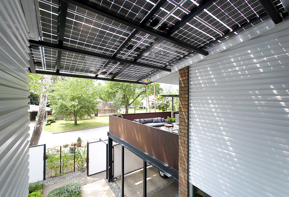 Thin-film photovoltaic solar panels create a generous entry porch roof cover with beautiful dappled light while generating electricity.