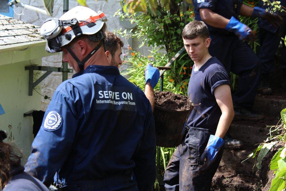 Serve On's Craig Elsdon helps Royal Navy volunteers clear mud from houses