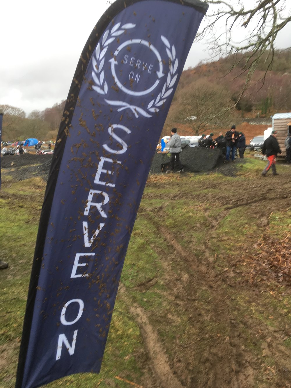 The mud-spattered Serve On flag still flew in spite of one of our disaster response tents being blown away by the gale force winds at the Dragon Rally in Snowdonia.