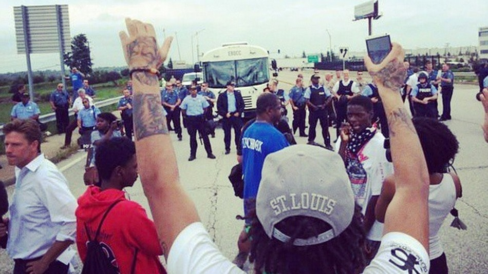 A protester raises both hands during the I-70 shutdown demonstration on Sept. 10.  IMAGE: @MEDIABLACKOUTUSA ON INSTAGRAM