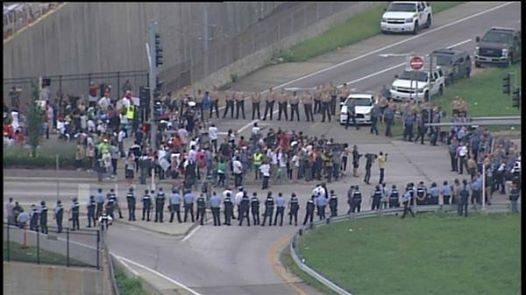 Law enforcement encircles the protestors to keep them off of I-70.