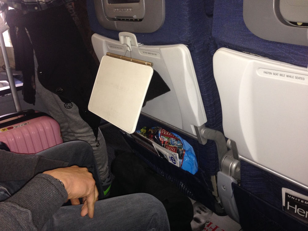 A use case study being conducted on a plane. This Loop iPad Case is hanging using the retractable cable on the back of a passengers seat. The user was able to adjust the angle of the iPad case for optimum viewing angle adjustments.