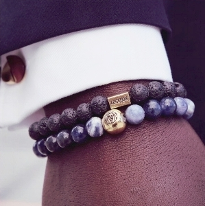 Photo of a black man's wrist with two beaded bracelets.