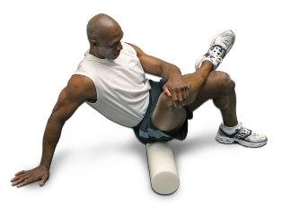 man rolt zijn bilspieren met een foam roller