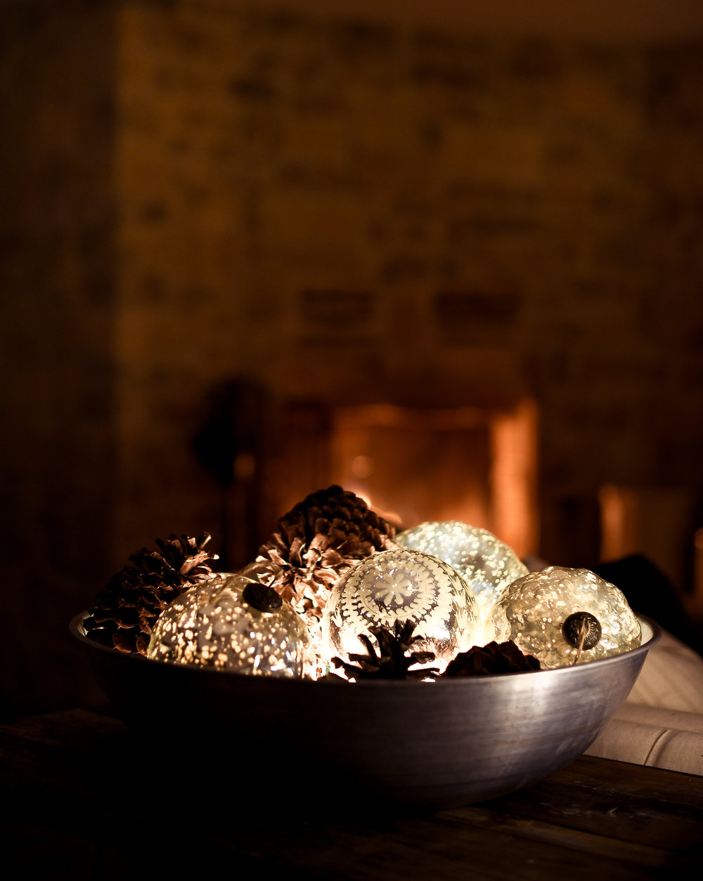 A bowl of mercury glass. - I absolutely love mercury glass, especially when it is lit up at night time! I filled my large zinc bowl full of oversized ornaments and pinecones which look beautiful at night!