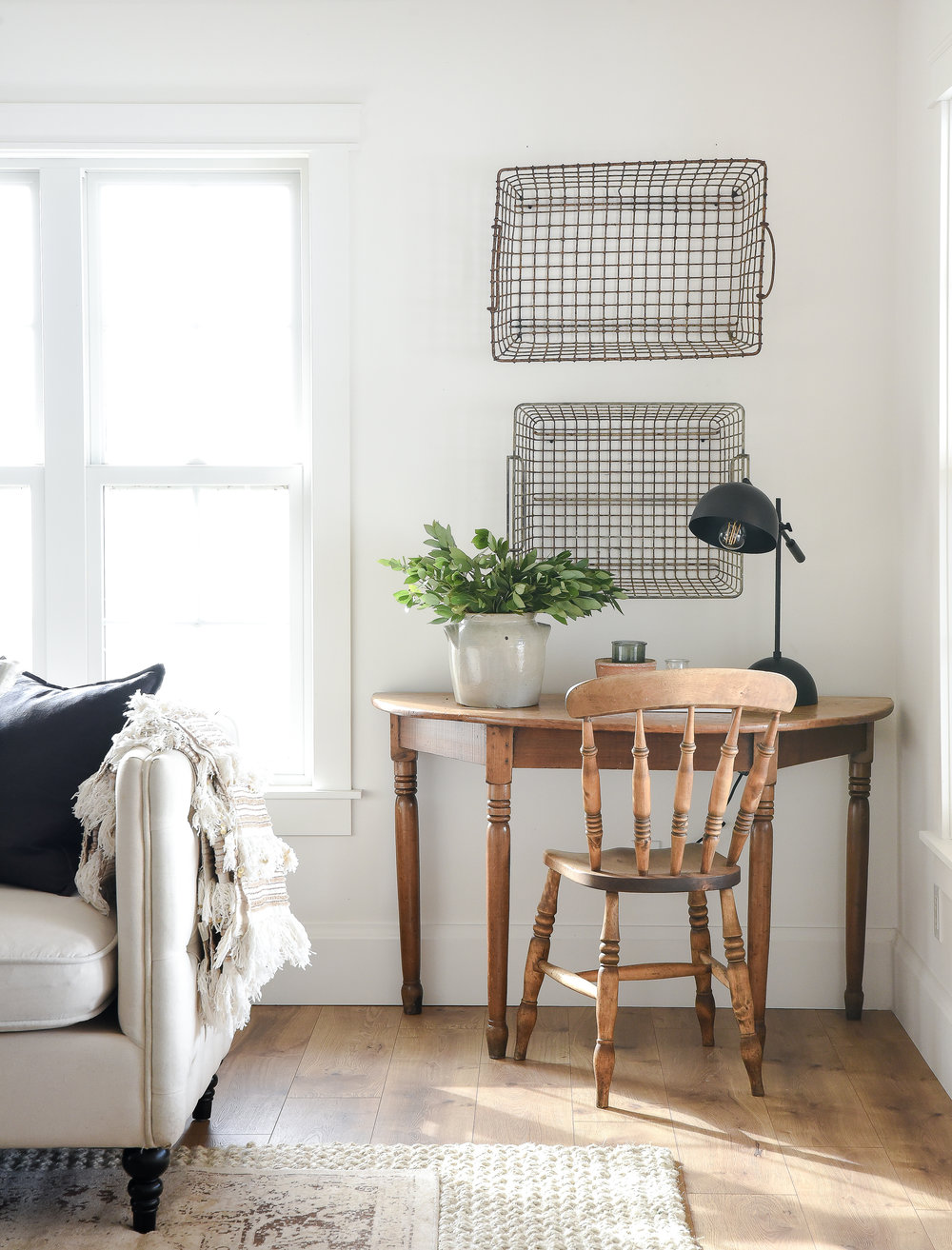 Farmhouse living room with antique wood desk and chair and vintage french oyster baskets next to layered rugs with crisp white walls. #farmhousedecor #farmhousestyle #livingroomdecor