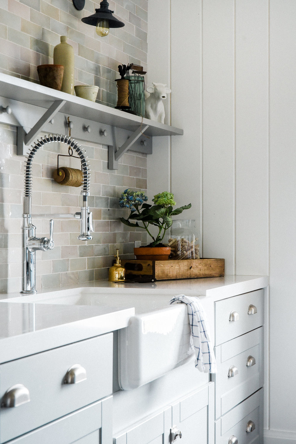 Laundry room remodel with gray cabinets and farm sink. White shiplap walls with shelf and cle tile. #laundryroom #farmhousestyle