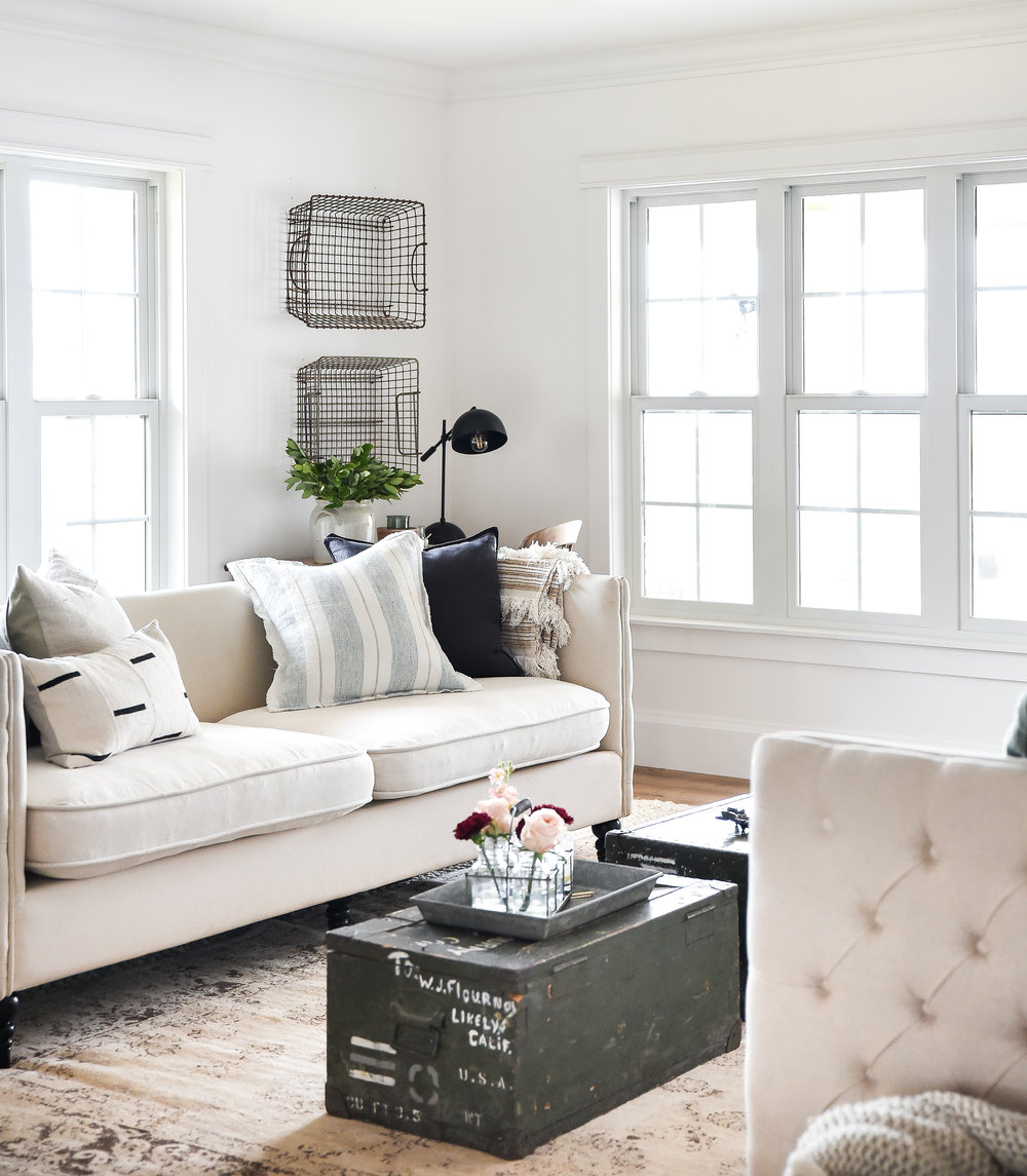 Farmhouse living room with vintage trunks, tufted couches, and vintage layered rugs. Linen pillows and crisp white walls with farm windows. #farmhousestyle #farmhousedecor #farmhouselivingroom
