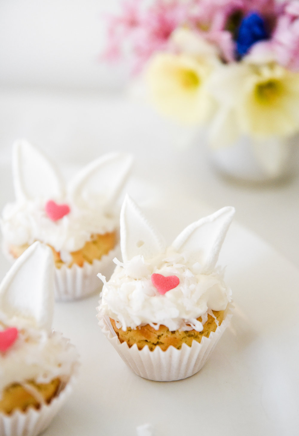 The sweetest Easter dessert idea! Easter bunny sugar cookies! Sugar cookies filled with a light and fluffy cream cheese frosting, topped with shredded coconut, and marshmallow bunny ears! boxwoodavenue.com #easterdessert #eastersugarcookies #bunnycookies