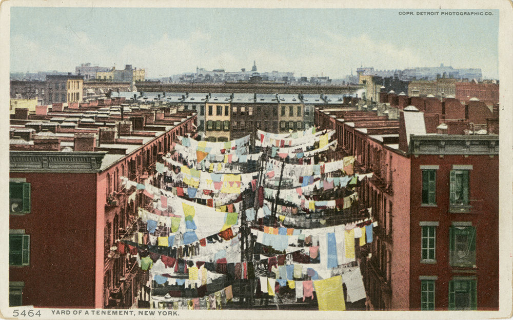 Laundry hangs between rows of tenements.