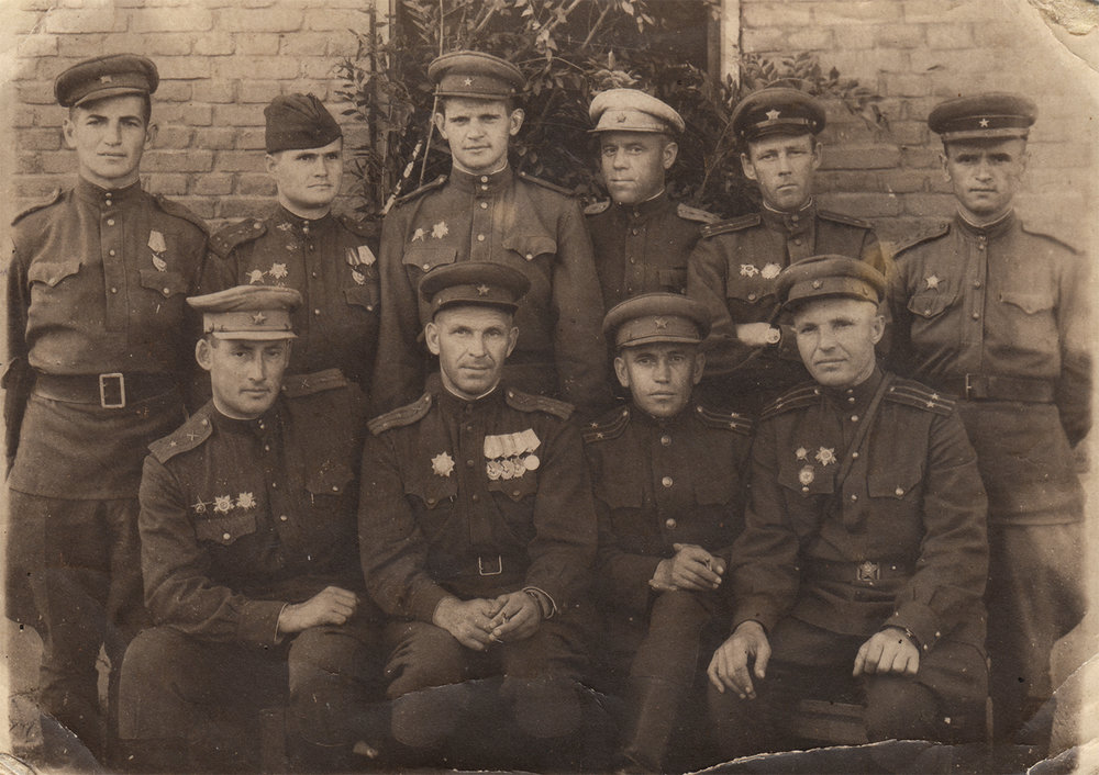 Artillery headquarters staff, separate rifle division, 221st Rifle Motor Corps [OG1]  . Yona Tsyganovsky is in the top row, first on the left. Germany, 1945   [OG1] I just put commas in there because I'm confused about the relationship between the different units and thus the prepositions, and I didn't see anything useful on Google. I think for something more specific you'd have to ask Yan.