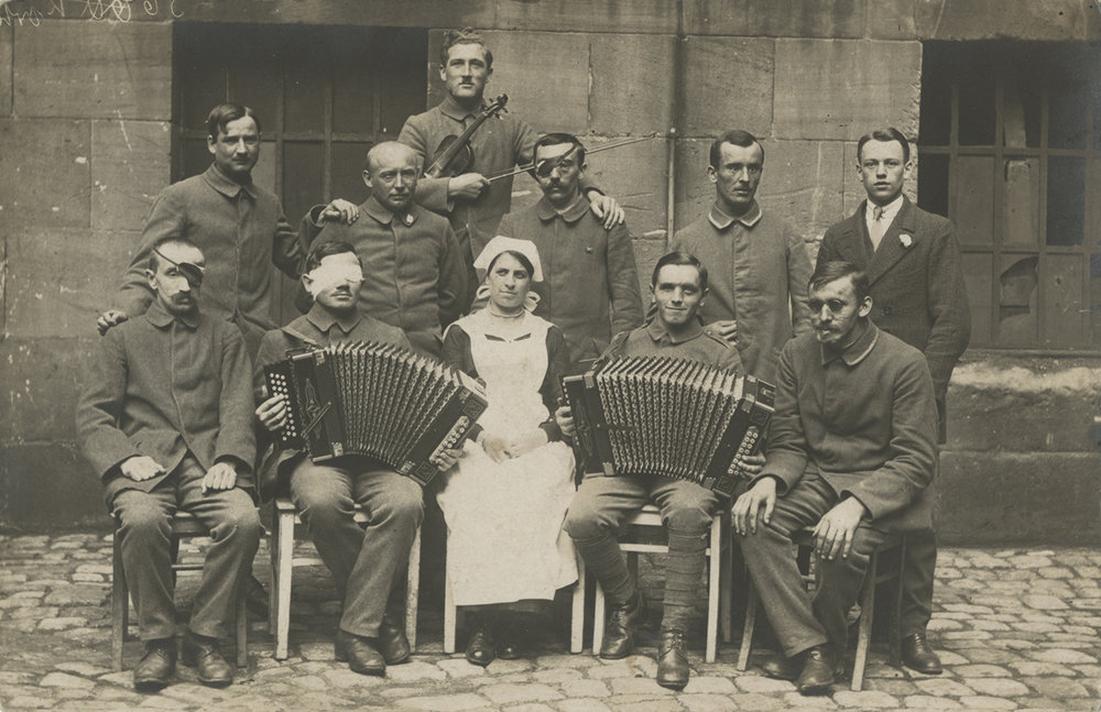 Wounded soilders with instruments and a nurse. ca. 1914-1918