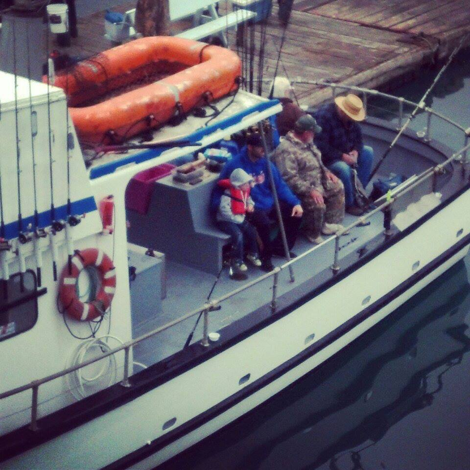 See our little cutie all bundled up on the end? Four hour fishing trip for our four-year-old.