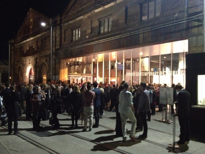 Last night's grand opening of the inaugural Sydney Contemporary Art Fair was an unmitigated success! The buzz could be felt blocks away, as throngs of smartly-dressed collectors descended upon the massive 19th century building, sexy moths to the flame of art. I've been to a lot of art fairs, all around the world, and can safely say that this one was pretty terrific. The fit out of the Carriageworks was top-notch – the white trade-fair style booths broken up by chunks of the original industrial architecture and graphic light installations. All the organisers – ownership, management and advisory – were walking around with big smiles on their faces, as were many of the gallerists. Red dots were popping up all over the place – rare, really on an opening night (most collectors prefer to come back and consider the choice they made in the thrill of an opening night). But not really surprising, given the quality of work on offer. In terms of the big, institutional installations, Candice Breitz' Working Class Hero (A Portrait of John Lennon) at Anna Schwartz Gallery is astonishingly beautiful – a 25-channel video installation of ardent Lennon fans singing a-capella to tracks from Lennon's Beatles breakaway album, John Lennon/Plastic Ono Band. Compelling. Equally mesmerising, though from a totally different perspective is the show of Wanjina paintings at Tim Klingender Gallery. Those big, black pools of eyes in these ancient figures feel out-of-time, spiritual. And for edgy European contemporary work, London's Paragon Art Publishers have a savvy selection of artist's prints, from the likes of Damien Hirst, Gary Hume, Dinos & Jake Chapman (including those space-Gothic figures that featured as embroideries in Louis Vuitton's menswear this season ;-) and It Boy de jour, Jonathan Yeo, whose painted portraits of fashion and cultural figures (from Sienna Miller to Rupert Murdoch) seem to have taken up the mantle of Lucien Freud for Generation Y. Great entry-level prices, too! That's just a quick snap shot of first impressions. I'm heading back out to Carriageworks for a more relaxed tour of the show. Stay tuned!