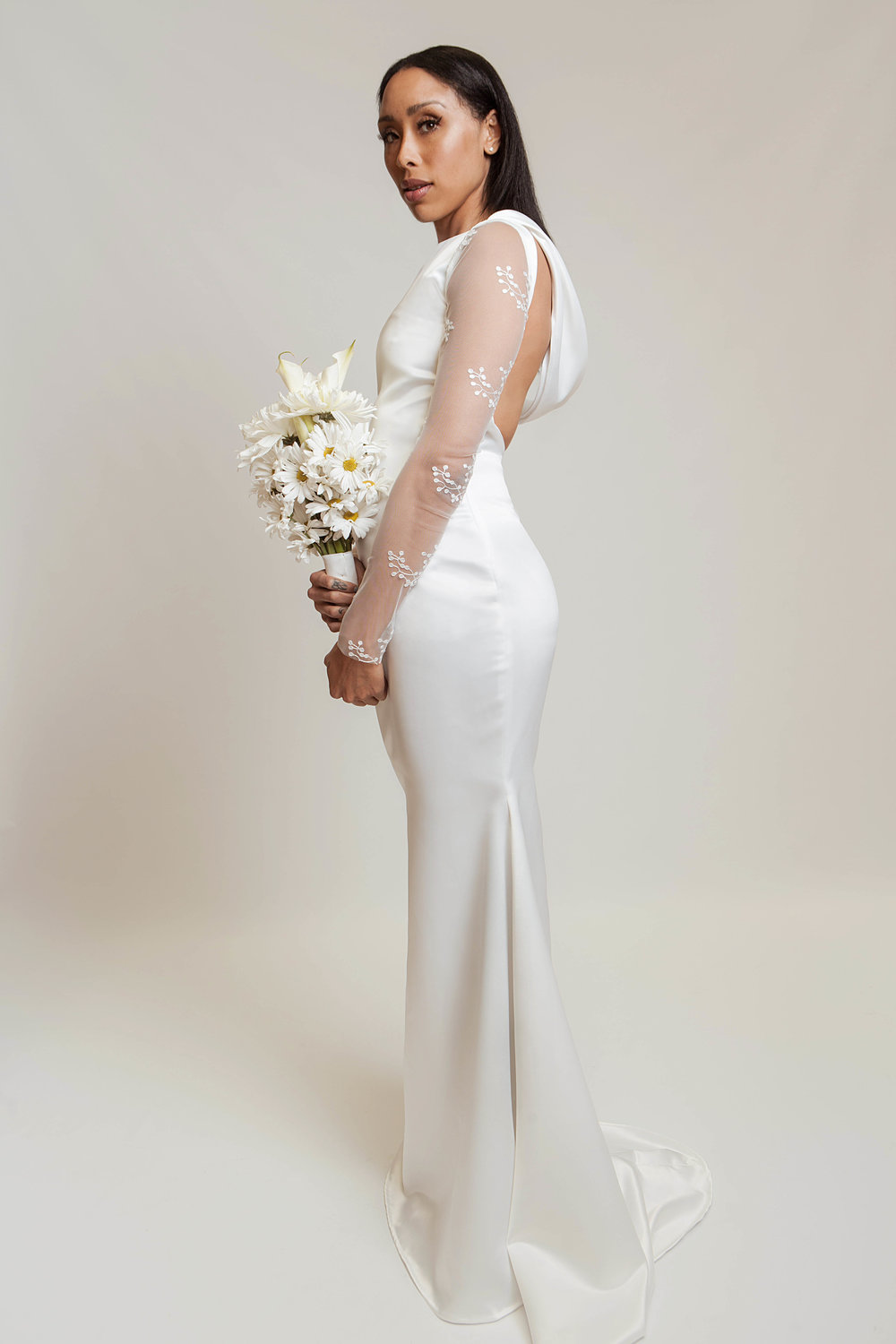 Mermaid style gown in a pearl white satin twill, stretch lace mesh sleeves, bias cut cowl neckline, and open back detail.