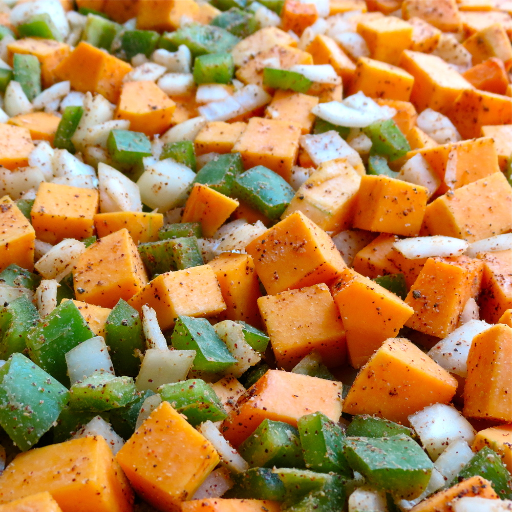 Squash and vegetables seasoned and ready for roasting.
