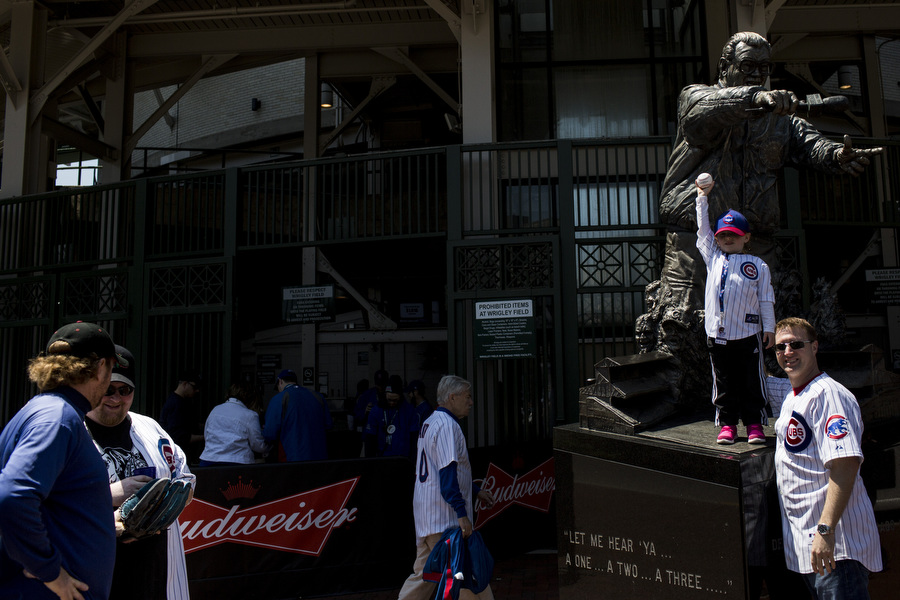 Chris Costello and his three-year-old daughter Madelynn pose for a Chicago Cubs photographer in front of the Harry Caray statue near the bleacher entrance. Sunday's game was Madelynn's first and she was given a game used ball by a fan who caught one during batting practice.
