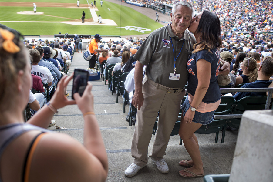 Drayonah Garza gives usher Bill Fundero a kiss on the cheek. Fundero has worked for the Tigers in some capacity since 1968.