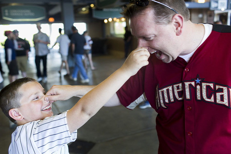 Mike Zimmerman and his 9-year-old son Mike pinch each other's nose before the game.