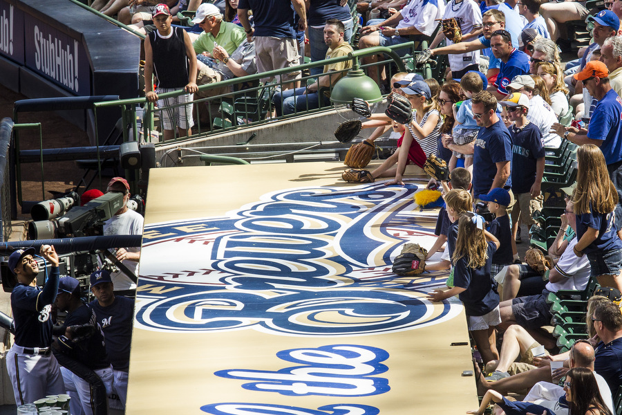 Brewers outfielder Carlos Gomez throws a ball to fans.