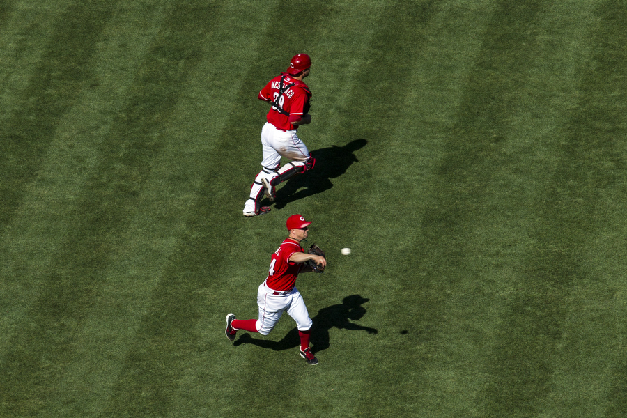 Reds pitcher Mike Leake throws to first on a weakly hit ground ball.