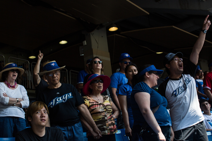 Glenn Gabriel, right, sings during the seventh inning stretch with his family.