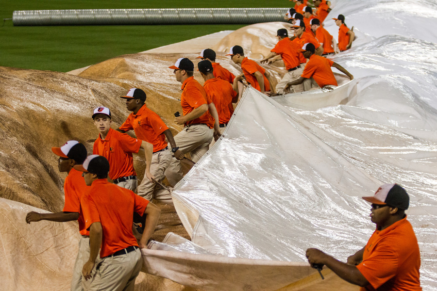 Members of the Orioles field crew pull the tarp over the infield during a rain storm.
