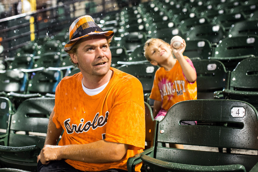 John Turpin and his four-year-old son Dylan sit in the bleachers during the rain delay.