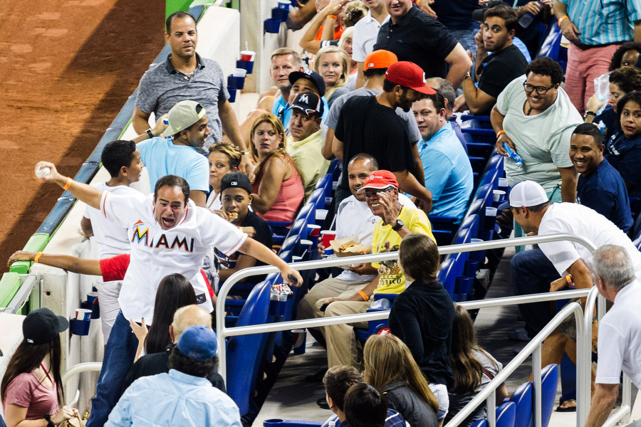 A man jumps in the air after catching a foul ball.
