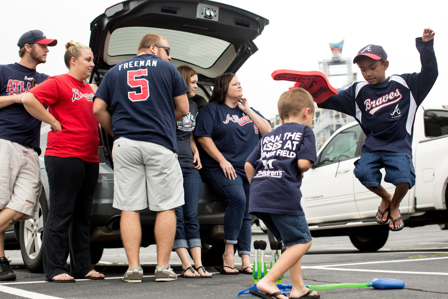 Jordan, right, and Peyton, second to the right, play with a Stomp Rocket in the Braves parking lot.