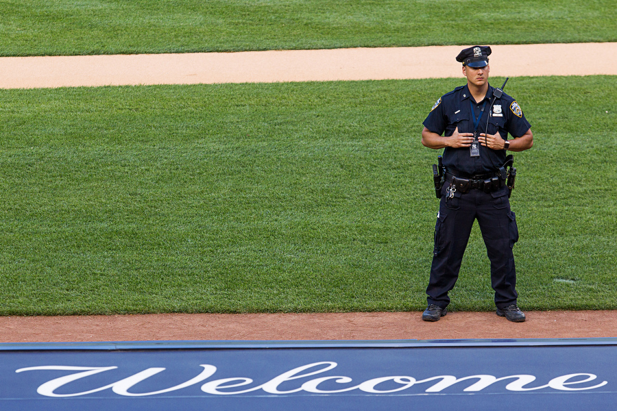 A policeman stands on the field before the game.