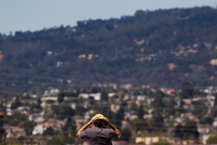 With the hills that lead to Redwood Regional Park in the background, a fan adjusts his cap.