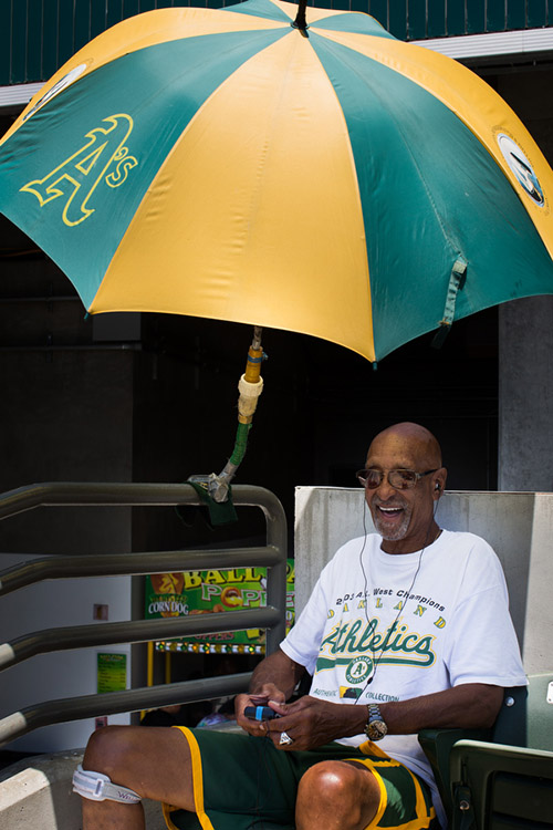 "Larry has been coming to A's games since 1968, when the team moved to Oakland. He's built a contraption that latches onto a piece of the bleachers and keeps an umbrella above his head.  ""I love the sun, but you bake,"" he said. ""I used to hold an umbrella but I said there's got to be a better way."" He remembers the 1970s fondly, recalling the ""Hot Pants Day"" promotion in which you were granted free entry to the game if you wore hot pants."