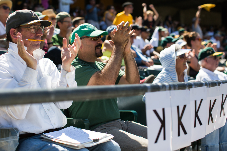 "Pete, left, k eeps score at all A's home games and in this game was posting a K on the railing for each strikeout recorded by an A's pitcher. He said he shares the ""K"" duty with other season ticket holders in Section 115. A manufacturing engineer for semiconductor company, Pete calls the scorecards a ""nice souvenir"" from the game. He brought along his friend Chuck, seated to his right."