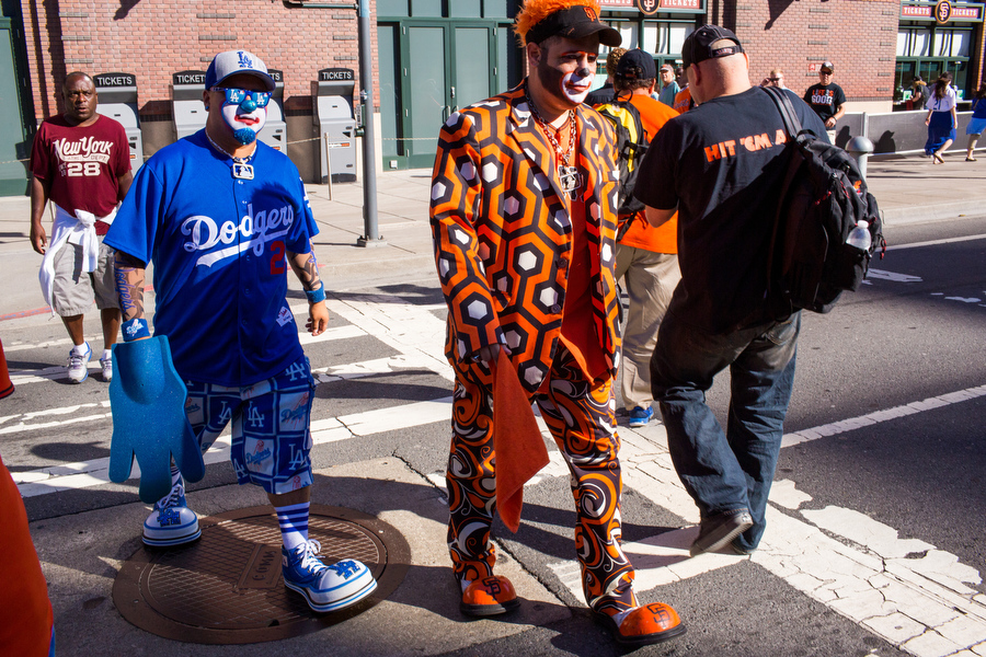 Clowns Hiccups, left, and Hoppers, right, cross the street before the game.