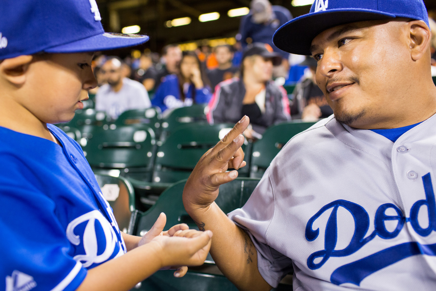 Rumaldo shows his son, Rumaldo Jr., how many more outs the Dodgers needed to secure the win.