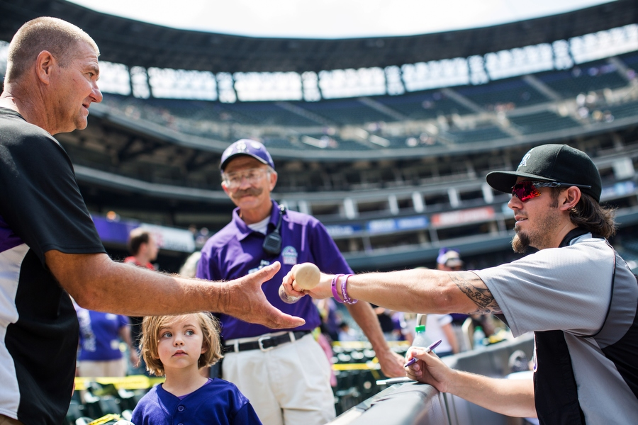 Rockies pitcher Christian Bergman hands a fan a bat after signing it. On home Sundays, the Rockies host autograph sessions.