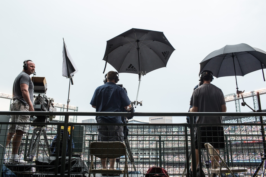Two television broadcast cameramen opened their umbrellas in anticipation of rain while one left his closed.