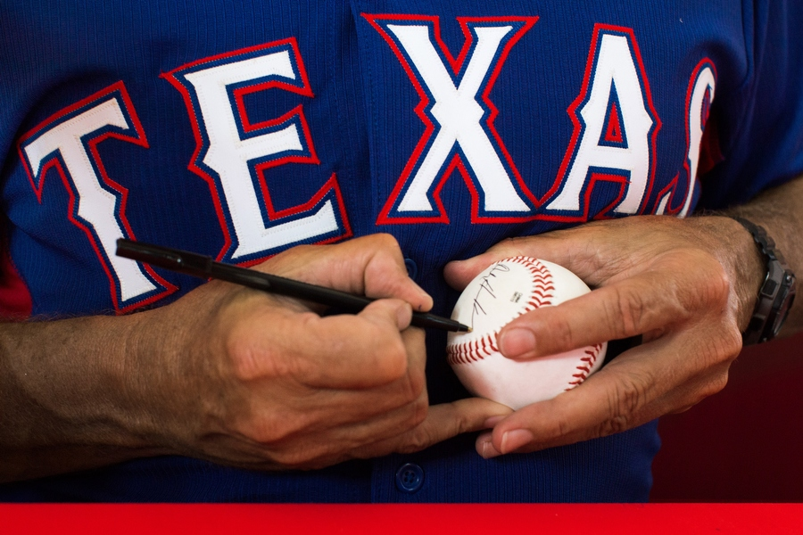 Bullpen coach Andy Hawkins signs a ball. The Rangers host autograph sessions with players and coaches on most Wednesday home games.