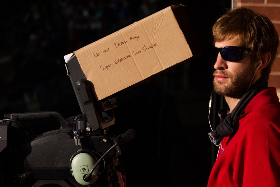 A cameraman uses cardboard to shield the sun from his monitor.