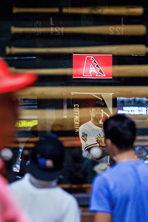 Fans look at an exhibit showing the process of making a bat from a piece of lumber.