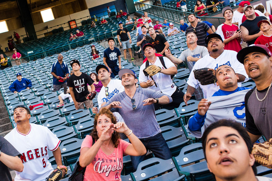 Fans prepare to catch an incoming home run ball during batting practice.