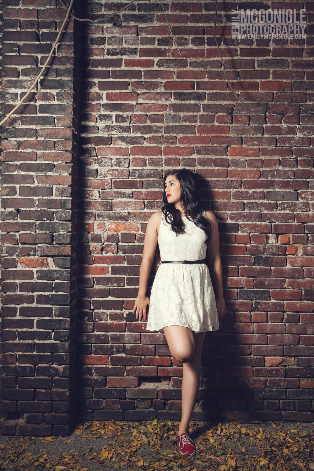 girl in white dress on brick wall