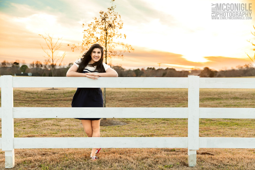 Senior girl on fence at sunset